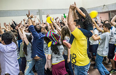 People with hands up interacting with Crowd Games
